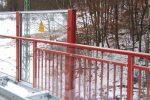 Das rote Geländer mit warnendem Aufkleber auf Plexiglas